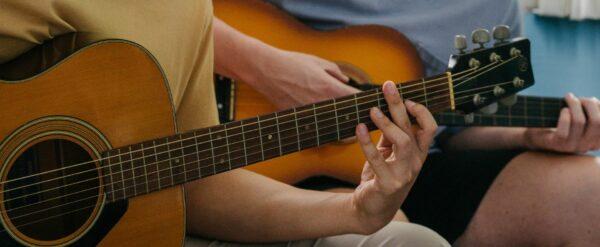 2 people playing guitar